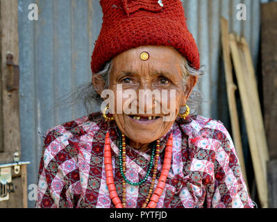 Very old Nepali Hyolmo woman with tooth gap and a massive golden bindi on her forehead. - Stock Photo