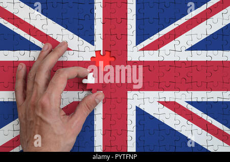 Great britain flag  is depicted on a puzzle, which the man's hand completes to fold. - Stock Photo