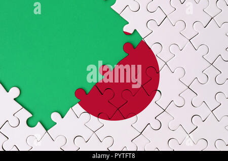 Japan flag  is depicted on a completed jigsaw puzzle with free green copy space on the left side. - Stock Photo