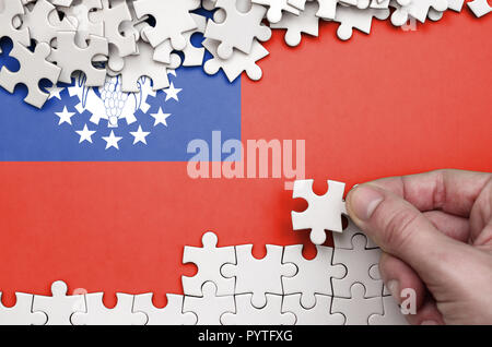 Myanmar flag  is depicted on a table on which the human hand folds a puzzle of white color. - Stock Photo