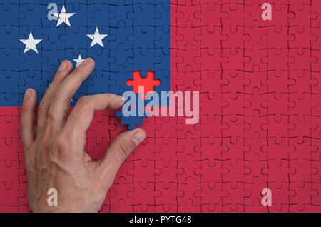 Samoa flag  is depicted on a puzzle, which the man's hand completes to fold. - Stock Photo