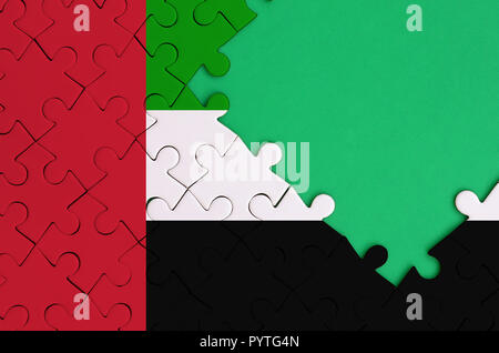 United Arab Emirates flag  is depicted on a completed jigsaw puzzle with free green copy space on the right side. - Stock Photo