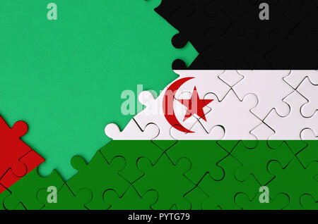 Western Sahara flag  is depicted on a completed jigsaw puzzle with free green copy space on the left side. - Stock Photo