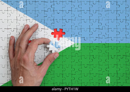 Djibouti flag  is depicted on a puzzle, which the man's hand completes to fold. - Stock Photo