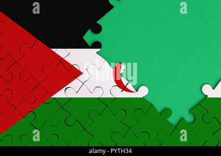 Western Sahara flag  is depicted on a completed jigsaw puzzle with free green copy space on the right side. - Stock Photo