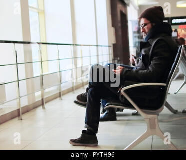 modern man with a laptop sitting at the airport - Stock Photo