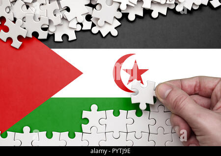 Western Sahara flag  is depicted on a table on which the human hand folds a puzzle of white color. - Stock Photo