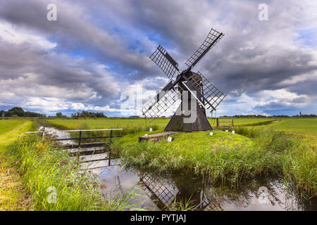 Traditional Wooden Windmill. This Historic water management pump device was used to drain water from a Polder, Netherlands - Stock Photo