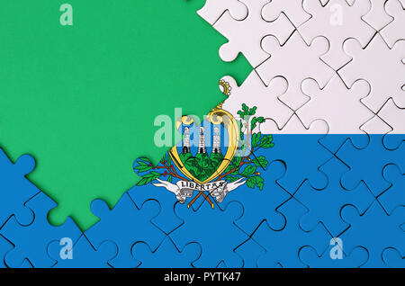 San Marino flag  is depicted on a completed jigsaw puzzle with free green copy space on the left side. - Stock Photo