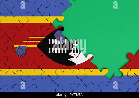 Swaziland flag  is depicted on a completed jigsaw puzzle with free green copy space on the right side. - Stock Photo