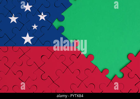 Samoa flag  is depicted on a completed jigsaw puzzle with free green copy space on the right side. - Stock Photo