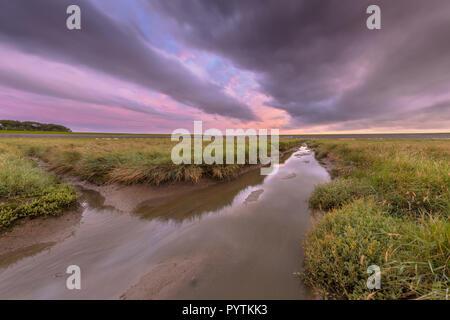 Sunset over graben creek in tidal marsh flat at Waddensea, Friesland, Netherlands - Stock Photo