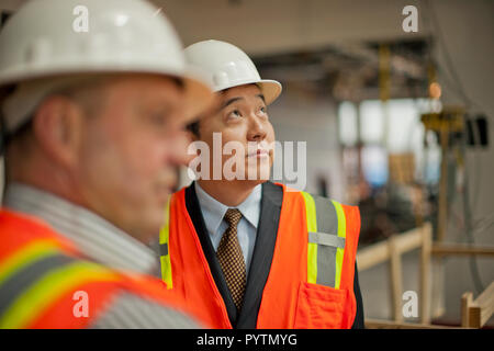 Middle aged businessman observing a construction site. - Stock Photo