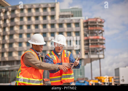 Two engineers in high visibility vests and hardhats discuss building plans on a construction site. - Stock Photo