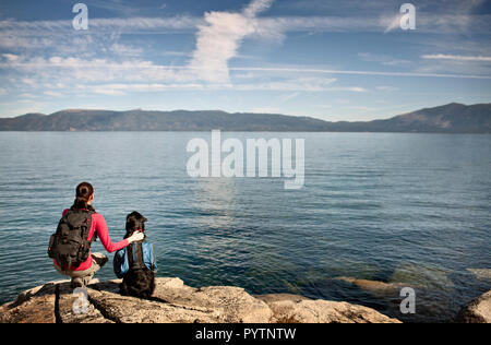 Mid-adult woman looking at beautiful lake with their dog.