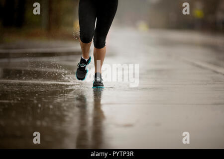 Young woman jogging on a residential street in the rain. - Stock Photo