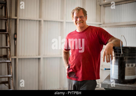Portrait of as mature man in a garage. - Stock Photo