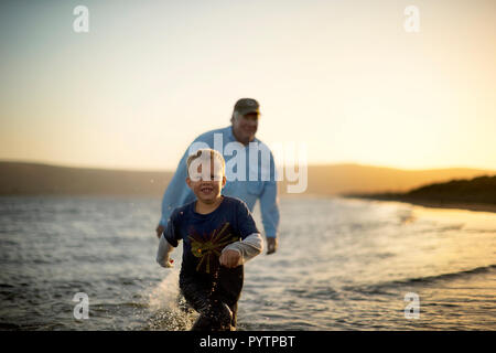 Portrait of a mature man playing in river with his young grandson and dog. - Stock Photo