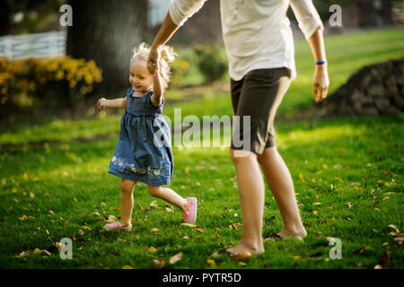 Happy young girl walking hand in hand with her mother. - Stock Photo