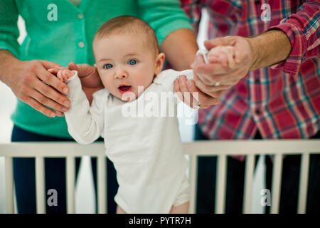 Cute smiling baby boy is supported by his parent's hands as they help him stand in his cot for the first time. - Stock Photo