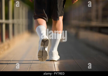 Feet walking on bleachers at a sports ground. - Stock Photo