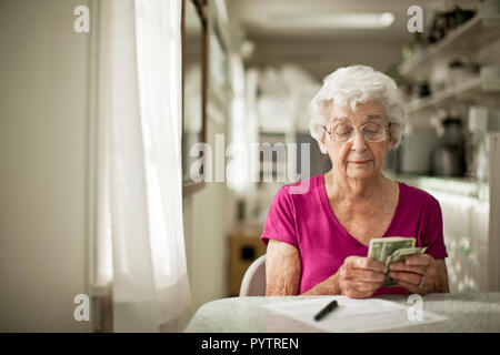 Anxious elderly woman sorts through her money to see if she has enough to pay the bill in front of her. - Stock Photo