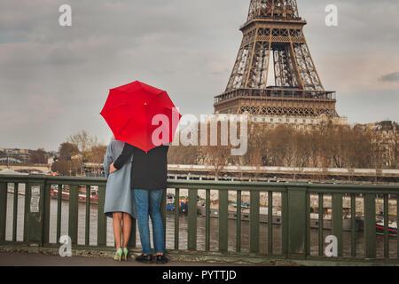 autumn in Paris, couple under red umbrella near Eiffel tower, fall season, love in rainy day, romantic moment on the bridge - Stock Photo