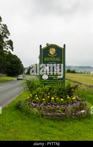 Welcome to Kendal sign and flowerbed on the A6 road, north east of Kendal. The sign highlights the town as winner of the Cumbria in Bloom competition. - Stock Photo