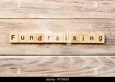 fundraising word written on wood block. fundraising text on table, concept. - Stock Photo