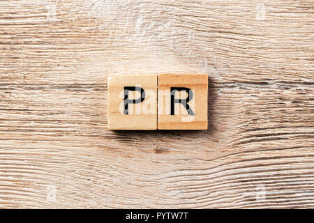 pr word written on wood block. public relation text on table, concept. - Stock Photo