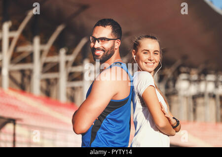 Portrait of multicultural handsome bearded man in blue shirt and sportish pretty blonde long haired woman in white t-shirt standing back to each other at the football stadium outdoor, healthy lifestyle and people concept