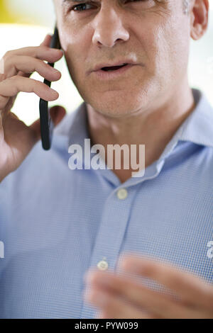 Frustrated Mature Man Receiving Sales Call At Home - Stock Photo