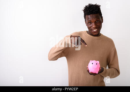 Studio shot of young happy black African man smiling while holdi - Stock Photo