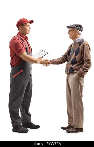 Full length profile shot of a mover shaking hands with a senior man isolated on white background - Stock Photo