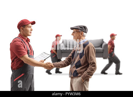 Senior man shaking hands with a mover, movers carrying a couch in the back isolated on white background - Stock Photo