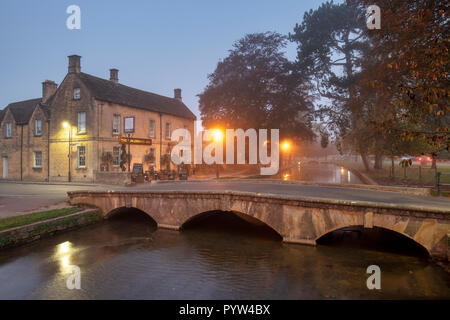 Mist and fog just after dawn in the cotswold village of Bourton on the Water in autumn. Bourton on the Water, Cotswolds, Gloucestershire, England - Stock Photo