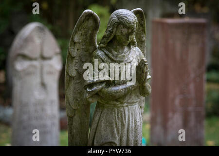 30 October 2018, Hessen, Frankfurt/Main: An angel sculpture stands on a grave. In the cemeteries there are more and more graves that have been left to their own devices for years. The reasons for this are different. (Zu dpa 'Neglected graves - relatives extend more rarely' of 30.10.2018) Photo: Boris Roessler/dpa - Stock Photo