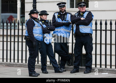 London, UK. 30th October, 2018. Police officers observe members and supporters of the Independent Workers of Great Britain (IWGB) trade union at a rally following a march with precarious workers from the offices of Transport for London to the University of London via the Court of Appeal in support of Uber drivers who are seeking employment rights. The Court of Appeal will today hear an appeal by Uber against a ruling that its drivers are employees rather than self-employed workers. Credit: Mark Kerrison/Alamy Live News - Stock Photo