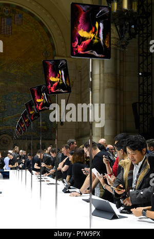 New York, USA. 30th Oct, 2018. People look at new Apple products during a launch event in Brooklyn, New York, the United States, on Oct. 30, 2018. Apple Inc. on Tuesday launched its new iPad Pro, MacBook Air and Mac mini at an event in Brooklyn, New York City, offering long-awaited updates to some of its popular devices. Credit: Xinhua/Alamy Live News - Stock Photo