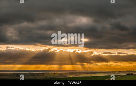 Firle, Lewes, East Sussex, UK. 30 October 2018..View from Firle Beacon in the South Downs looking over Seaford & Rampion offshore wind farm as the sun breaks through cloud cover shortly before sunset. Much colder now with a stiff breeze from the North East.. - Stock Photo