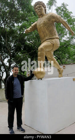 Buenos Aires, Argentina. 30th Oct, 2018. Cesar Perez, promoter of the tribute to Diego Armando Maradona, poses next to the statue of the Argentine icon, the day of the birthday of the Argentine player, in Buenos Aires, Argentina, 30 October 2018. An imposing mural and a large statue of Diego Armando Maradona were located a few meters from the stadium of Argentinos Juniors, in the neighborhood of La Paternal, where the world champion in Mexico 1986 debuted, who turns 58 today. Credit: Sebastian Meresman/EFE/Alamy Live News - Stock Photo