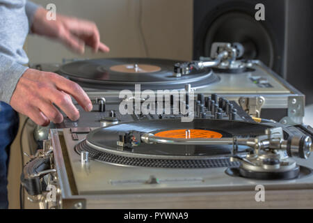 Hands of DJ playing music from vinyl records in his home studio - Stock Photo