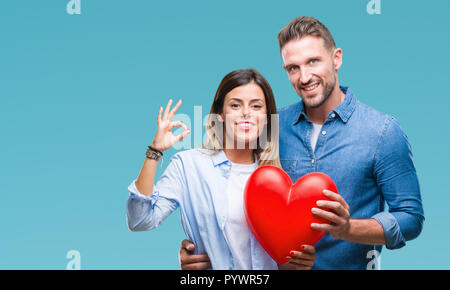 Young couple in love holding red heart over isolated background doing ok sign with fingers, excellent symbol - Stock Photo