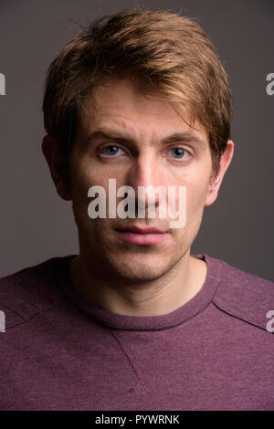 Portrait of handsome man against gray background - Stock Photo