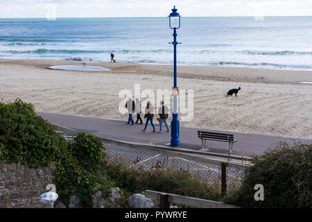 People & dogs out for a sunday afternoon walk along Bournemouth promenade & beach on a chilly day in October 2018, Dorset, UK - Stock Photo