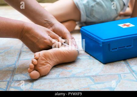 Woman puts adhesive bandage on child foot. - Stock Photo