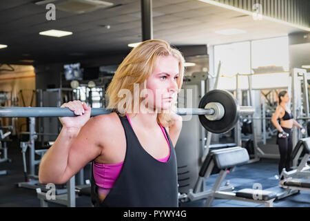 Young fit woman at the gym doing heavylifting exercise. Female athlete at a fitness room working out with barbell - Stock Photo