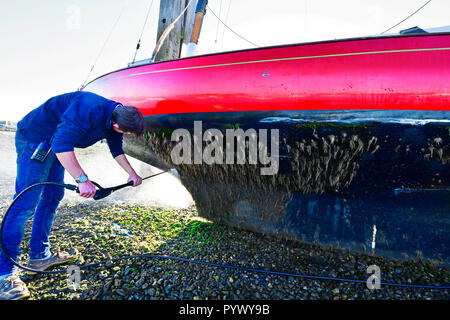 Man pressure hosing excessive algea weed growth off the hull of his X boat,Madame x )  as it rests against Itchenor's scrubbing off Dolphins - Stock Photo