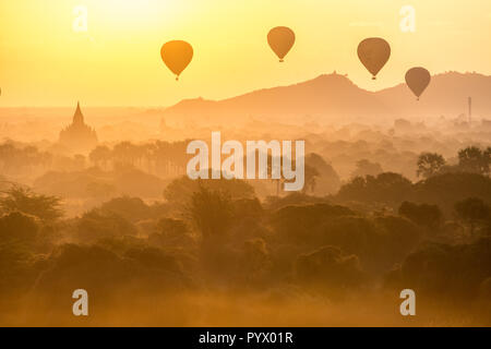 Air balloons flying over pagodas at misty dawn in the plain of Bagan, Myanmar - Stock Photo