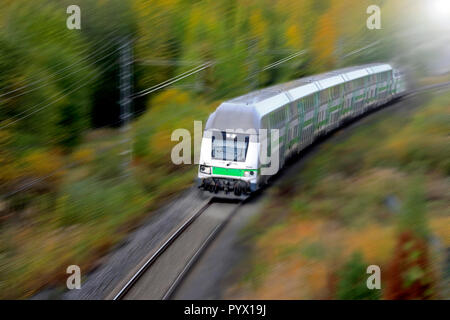 Passenger train at speed in autumn, elevated view, motion blur. - Stock Photo